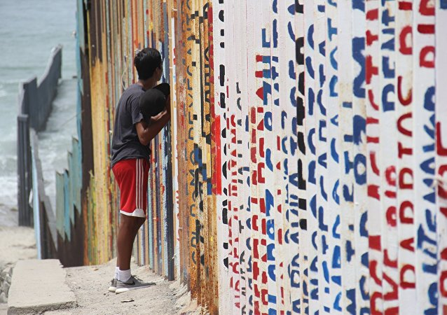 Un joven habla con sus familiares a través del muro que separa México y EEUU (archivo)