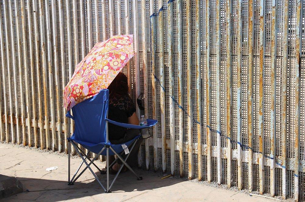 Una mujer habla con sus familiares a través del muro que separa México y EEUU