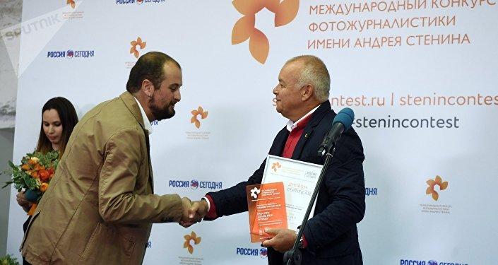 Ganador del Concurso Internacional de Fotoperiodismo Andréi Stenin, Alejandro Martínez Vélez, y el director general de Sputnik, Dmitri Kiseliov