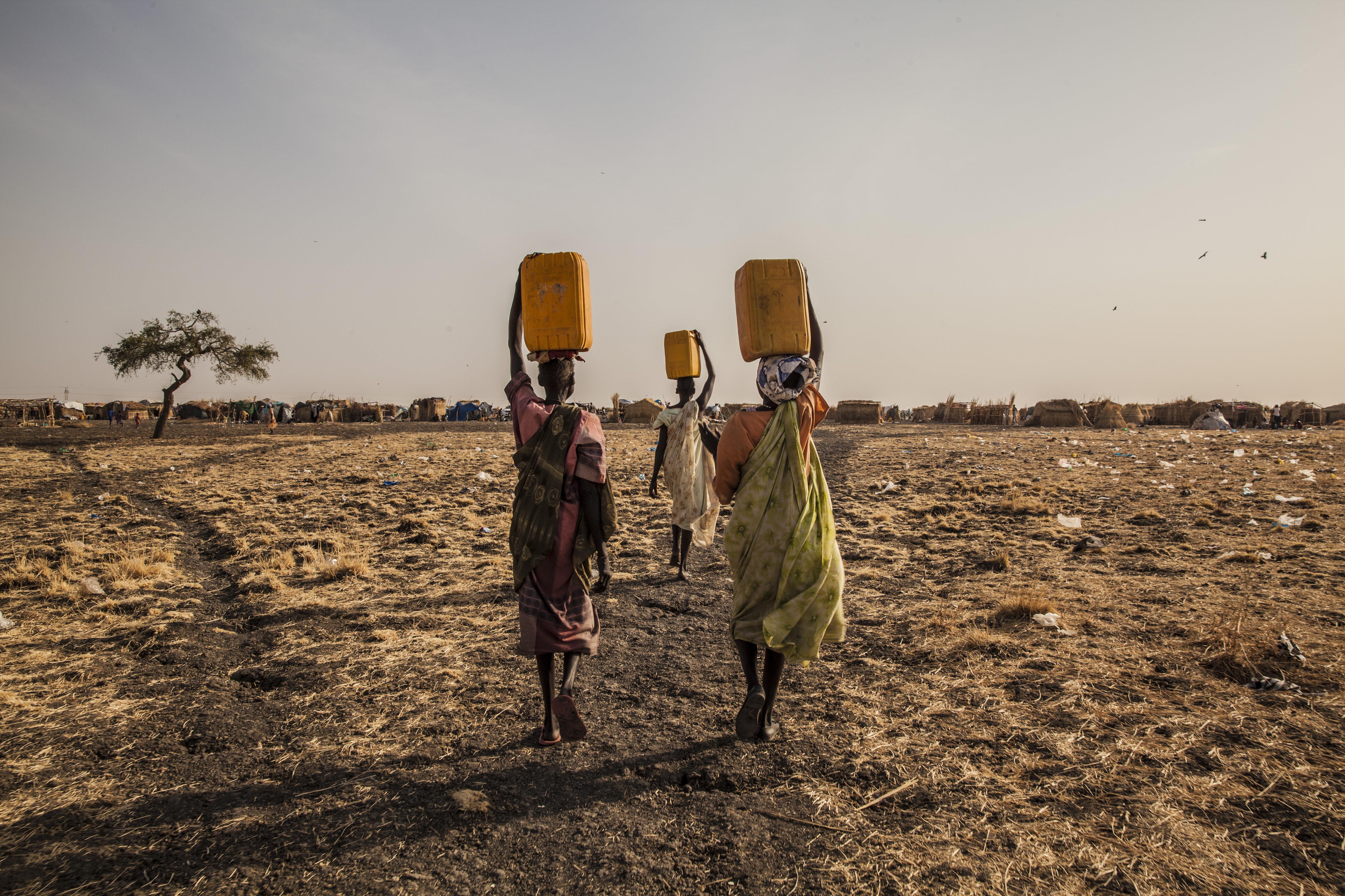 Tres mujeres llevando agua en un campo de desplazados en Melut, Sudán del Sur
