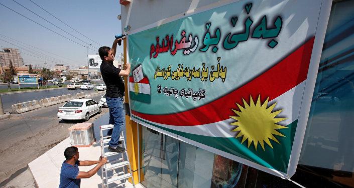 Los kurdos iraquíes ponen un cartel llamando a votar en el referéndum independista