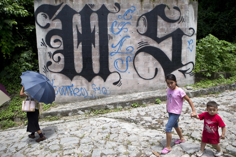 Unos niños pasean al lado de un muro pintado con los símbolos del MS-13 en El Salvador (archivo)