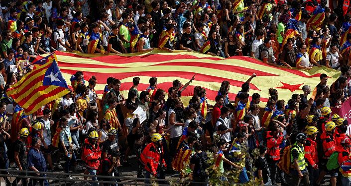 Estudiantes llevan una bandera separatista catalana mientras asisten a una manifestación en favor del referéndum de independencia