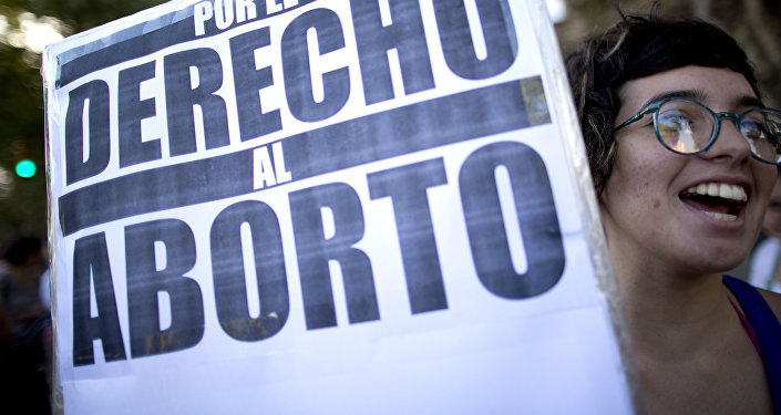 A woman holds a banner that reads in Spanish For the right to abort, during a rally in Buenos Aires, Argentina