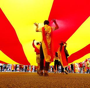 La gente camina debajo de la bandera de Cataluña