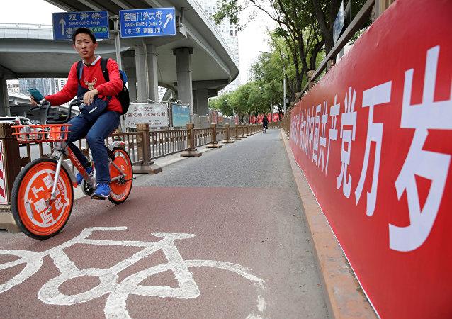Un ciclista chino cerca del cartel que dice Que viva el gran partido Comunista de China
