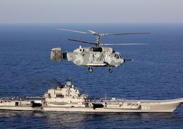Un Ka-29, con el Almirante Kuznetsov de fondo, en el Mediterráneo