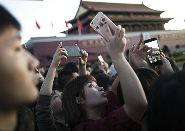 Una joven china sacando una foto con un teléfono móvil en Pekín