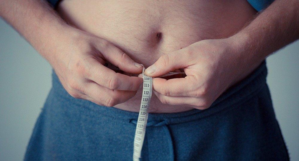 Un hombre se mide la barriga con una cinta métrica