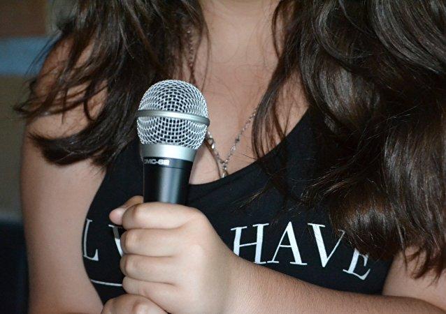 Una mujer con micrófono (imagen referencial)