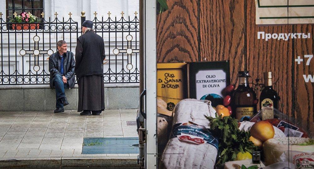 Un camión que anuncia productos de comida italiana pasa frente a una iglesia ortodoxa rusa