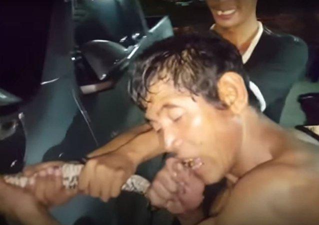 Un hombre muerde a una pitón