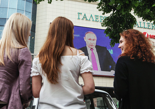 Unas jóvenes rusas están viendo un discurdo del presidente de Rusia, Vladímir Putin, por la televisión