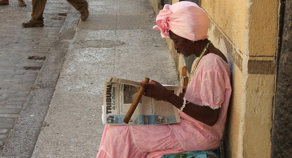 Una mujer cubana lee y fuma un puro en las calles de La Habana (imagen referencial)