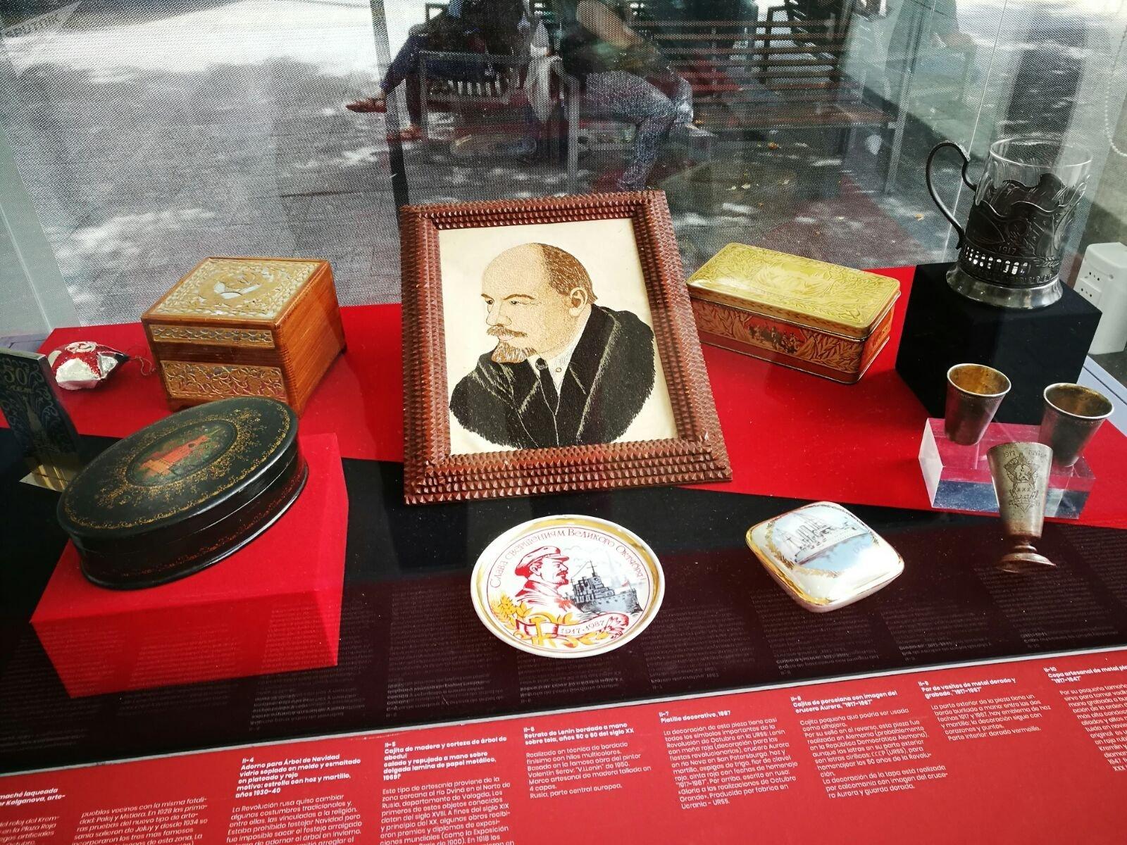 Artesanías de la época soviética en la muestra '100 años de Octubre Rojo', en Montevideo, Uruguay, con un retrato de Lenin bordado en destaque.