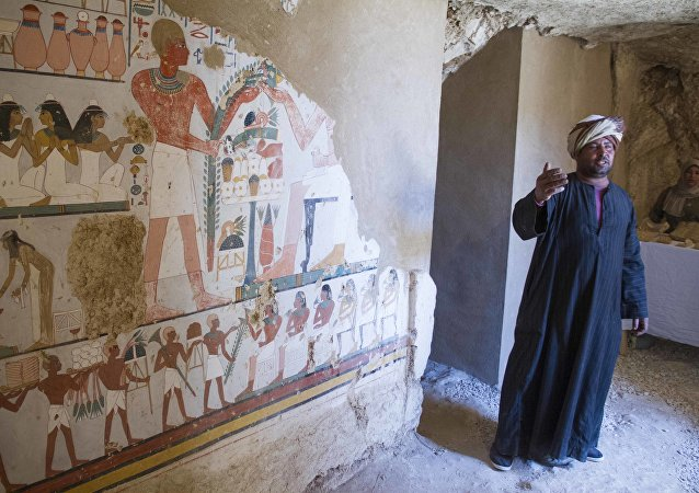 Un guardia egipcio junto a un mural finenrario en el interior de la tumba Kampp 161 el día del anuncio del ministro de Antigüedades de Egipto
