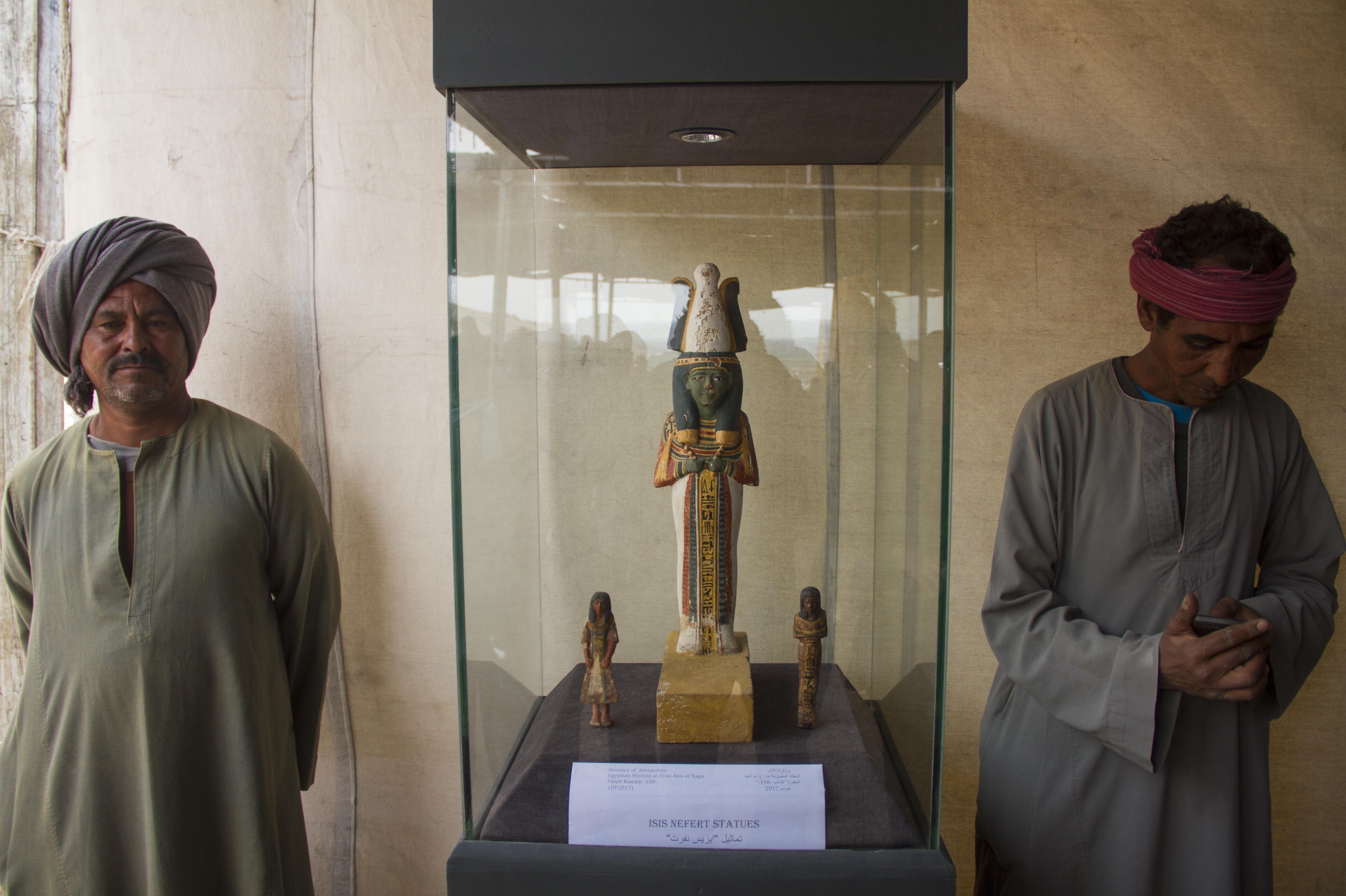 Dos excavadores egipcios custodian una estatua de madera en la tumba Kampp 161