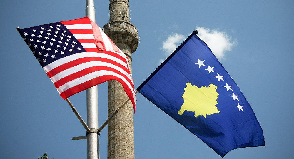 A minaret is seen through American and Kosovo flags that decorate the streets of Kosovo's capital Pristina