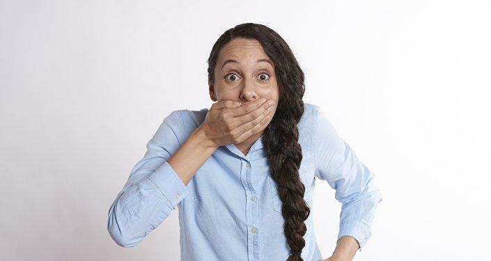 Una mujer tapándose la boca