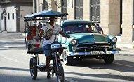 Un bicitaxi y un almendrón (auto antiguo) en La Habana
