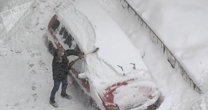 Un hombre está limpiado su auto de la nieve en Moscú