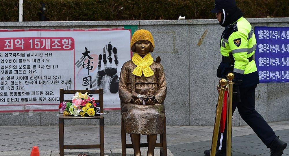 Un policía surcoreano pasa por delante de la estatua de una joven con un vestido tradicional representando a las 'mujeres de consuelo' que sirvieron como esclavas sexuales durante la II Guerra Mundial.
