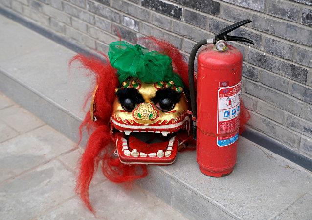 Una máscara de león y un extintor de incendios en Pekín, China