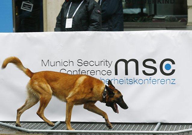 El perro policiaco cerca del logo de la Conferencia de Seguridad de Múnich
