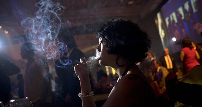 Mujer fuma un puro durante del Festival Internacional del Habano en Cuba