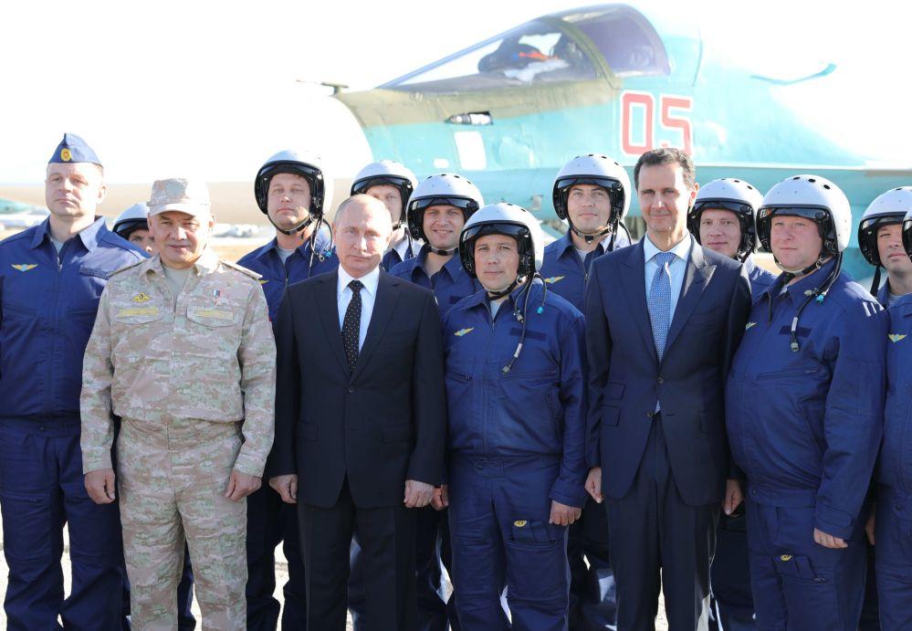 El presidente de Rusia, Vladímir Putin, el presidente de Siria, Bashar Asad, y el ministro de Defensa ruso, Serguéi Shoigú, fotografiados con los militares rusos durante una visita a la base aérea de Hmeymim, en Siria