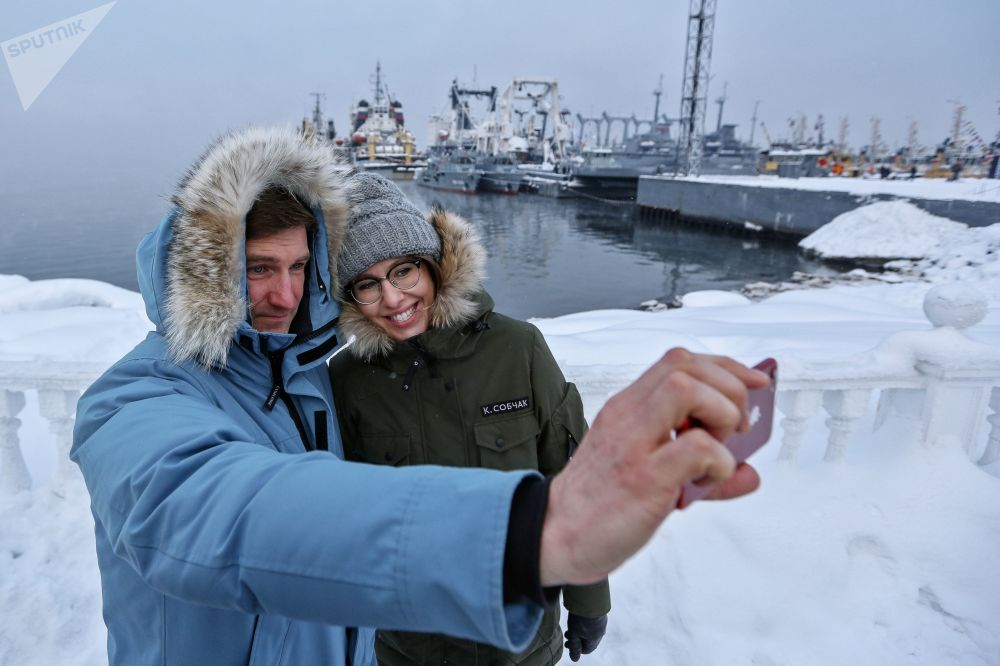 La presentadora de televisión y candidata presidencial por el partido Iniciativa Civil, Ksenia Sobchak, y un miembro de su equipo de campaña, Antón Krasovski, se toman una foto frente a unas naves en la ciudad de Severomorsk, en la región de Múrmansk