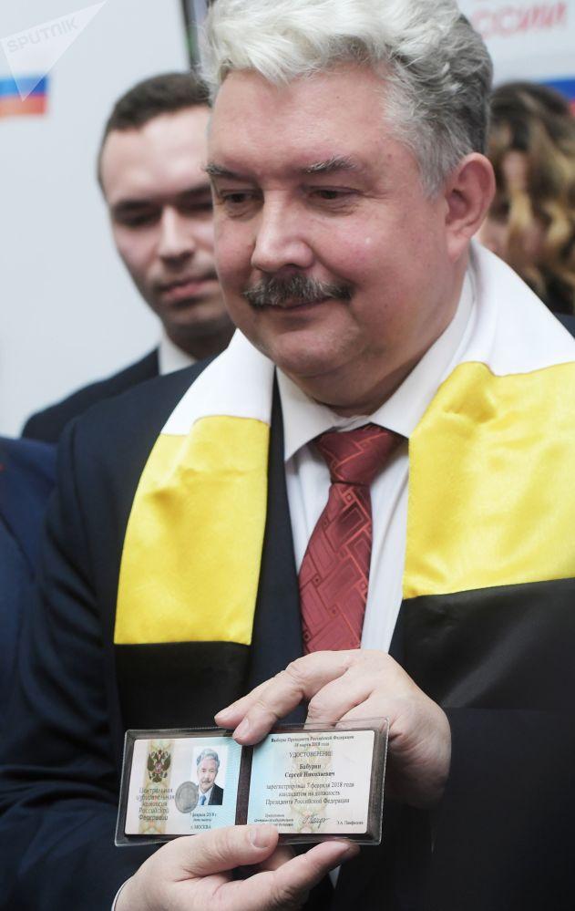 Serguéi Baburin muestra su certificado de registro como candidato presidencial de Rusia