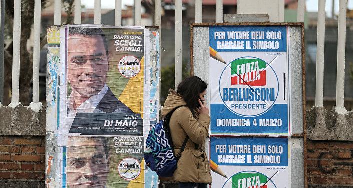 Una mujer camina por delante de afiches electorales en Pomigliano D'Arco, cerca de Nápoles.