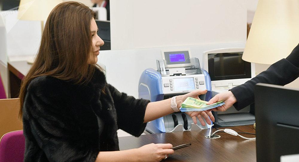 Una mujer recibe dinero en un banco en Moscú, Rusia