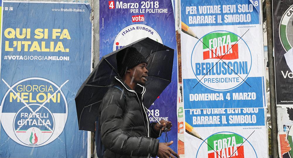 Un inmigrante africano pasa ante carteles electorales para las elecciones generales de Italia