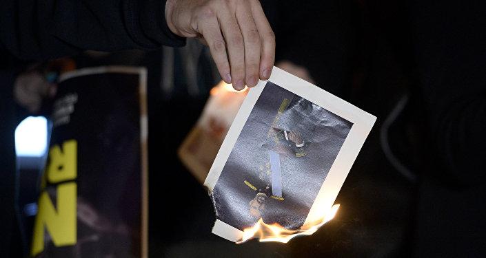 Un manifestante quema una foto del Rey de España, Felipe VI (archivo)