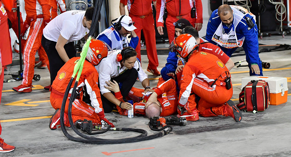 Un mecánico de Ferrari es atendido por sus compañeros después de un accidente durante durante el Gran Premio de Bahréin de F1