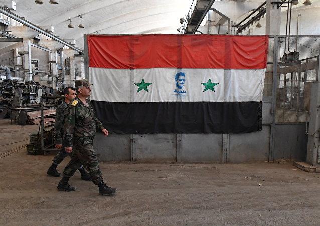 Militares sirios pasan ante la bandera del país (archivo)