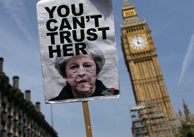 Un cartel con la foto de la primera ministra del Reino Unido que dice: No pueden fiarse de ella