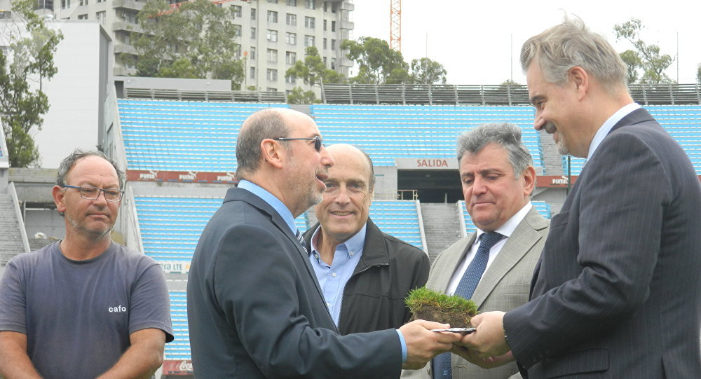 El subsecretario Nacional de Deporte de Uruguay, Alfredo Etchandy, hace entrega al embajador de Rusia en Montevideo, Nikolái Sofinski, de un pan de césped del histórico estadio Centenario