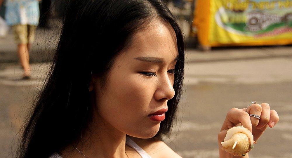 Mujer tailandesa come en la calle