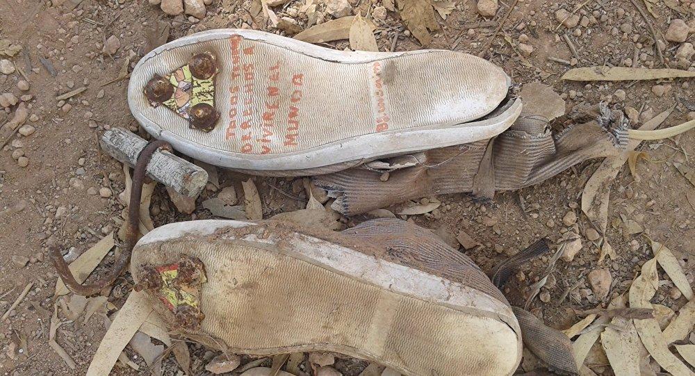 Fotografía de unas zapatillas con clavos en las suelas y un garfio de metal, que los inmigrantes indocumentados utilizan para saltar las vallas de Ceuta y Melilla, España.