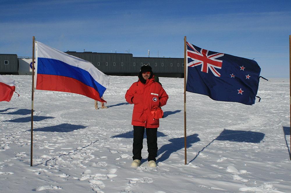 Alexandr Nóvikov, investigador de la Universidad Nacional de Investigaciones Nucleares de Rusia (MEPhI), junto a las banderas de Rusia y de Nueva Zelanda, países participantes en los estudios en la Antártida
