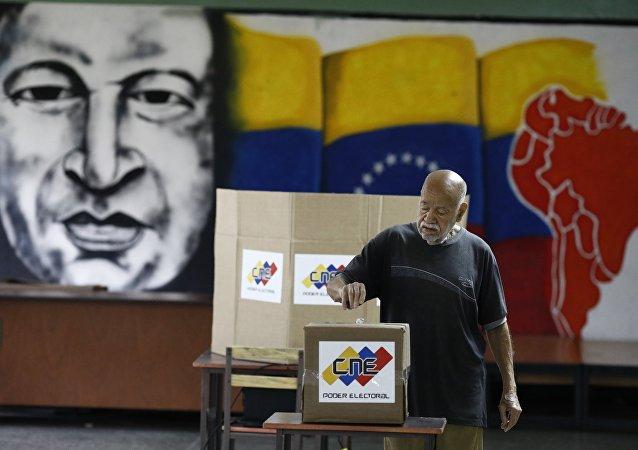 Un venezolano está votando en las elecciones presidenciales en Caracas con una imagen del expresidente del país, Hugo Chávez, de fondo