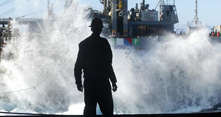 Un marino mira en una enorme ola que aparece del USS Harry S. Truman
