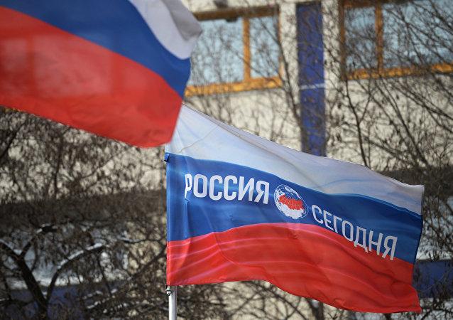 Bandera rusa con el logotipo de la Agencia de Información Internacional Rossiya Segodnya