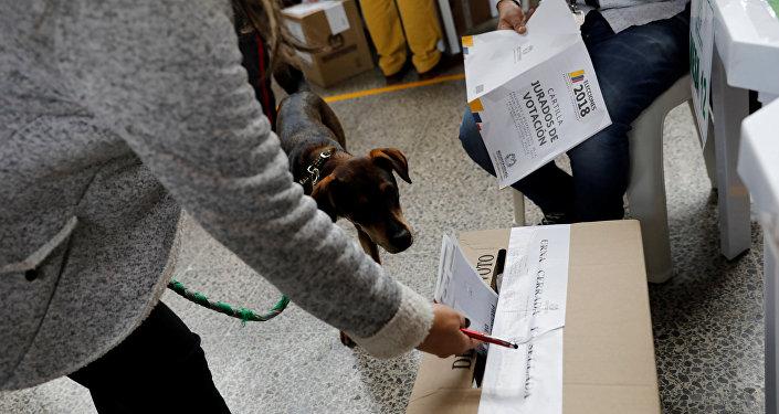 Una colombiana vota con su perro durante las elecciones del 27 de mayo