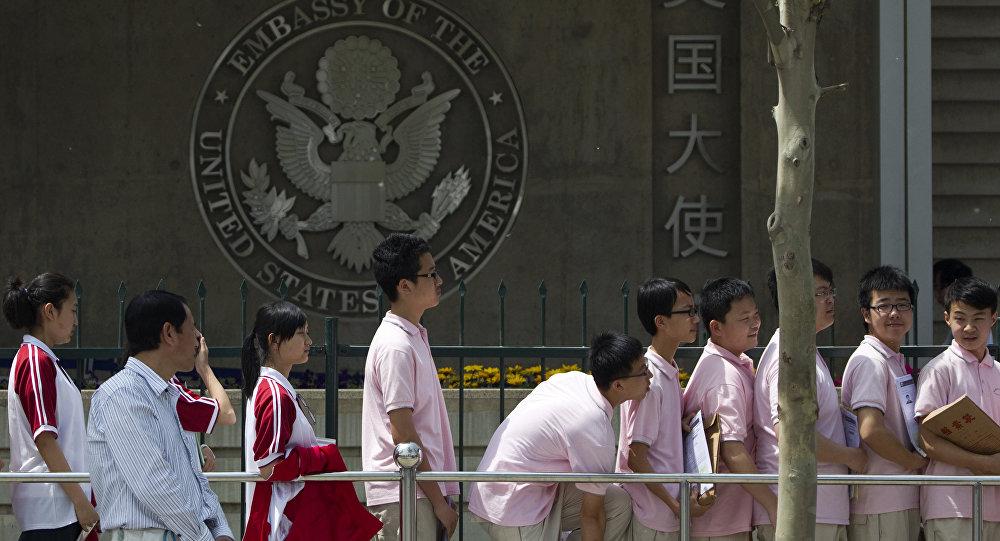 Los estudiantes chinos esperan sus entrevistas para recibir su visa en las afueras de la Embajada de EEUU, en Pekín