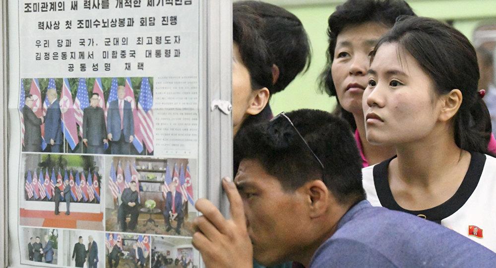 Los norcoreanos leen en un periódico sobre la cumbre entre EEUU y Corea del Norte