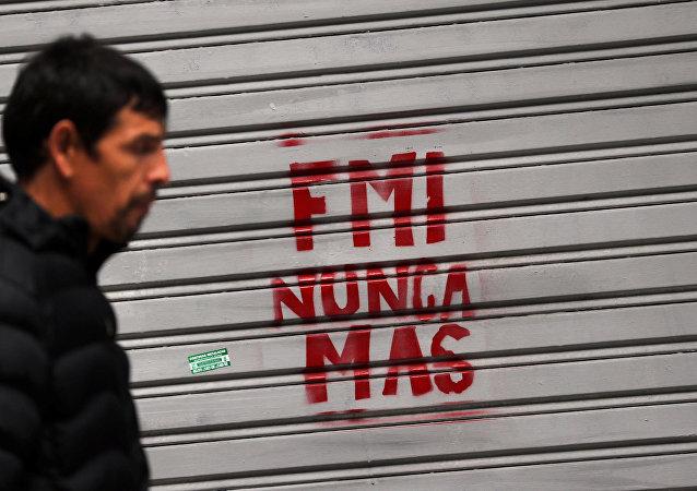 Un hombre camina frente a un grafiti de protesta contra el FMI